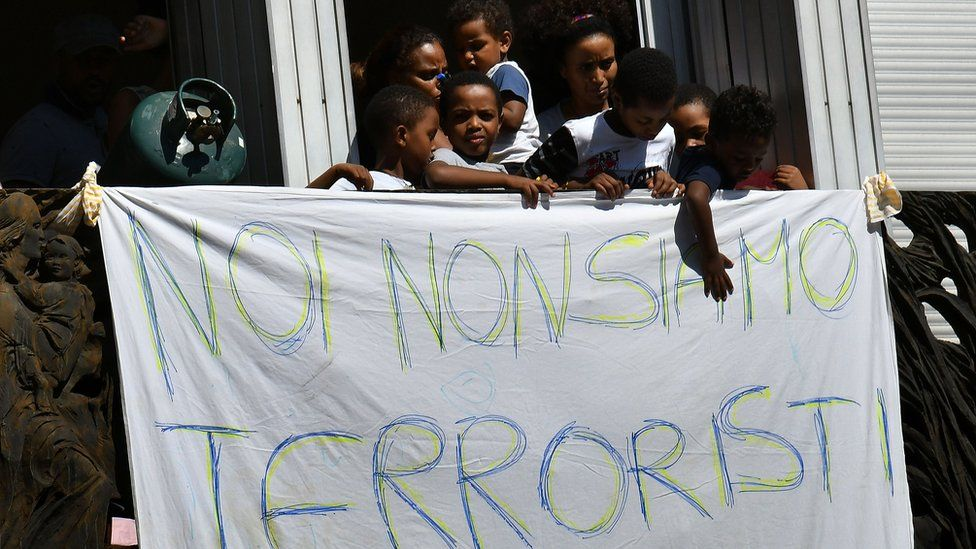 Refugees and asylum seekers protest against their eviction near gas cylinders and a banner reading 'We are not terrorists' on 23 August 2017