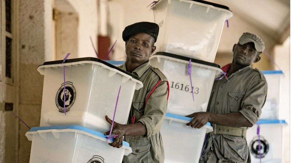 Security workers carry ballot boxes at a polling station in Dar es Salaam on October 26, 2015.