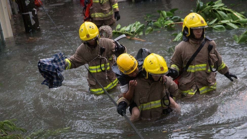 Rescuers carry a woman across a flooded street in Hong Kong