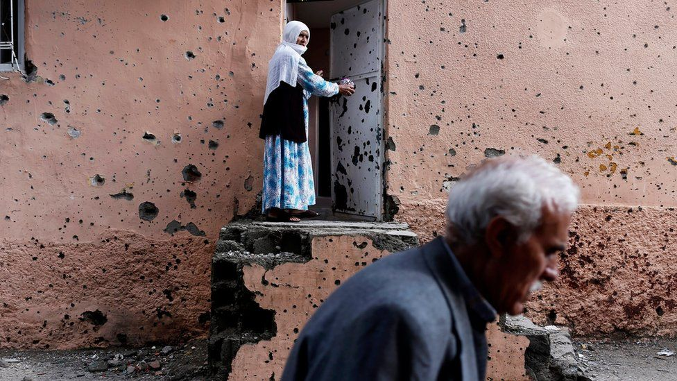 A Kurdish woman stands beside the bullet-riddled wall of her house in Diyarbakir, south-eastern Turkey (30 October 2015)