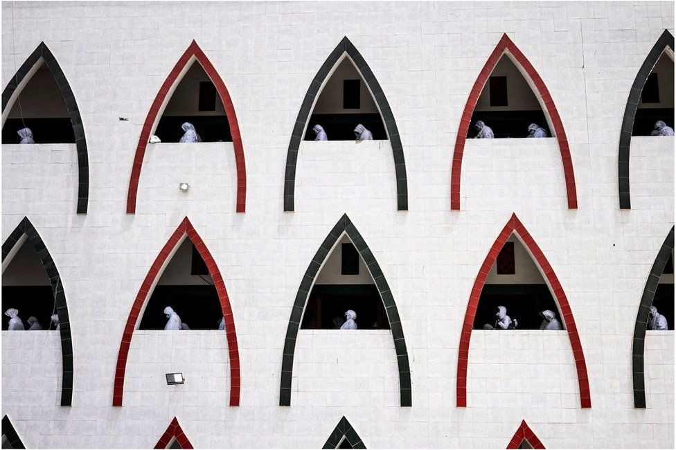 Muslim worshippers are seen through triangle-shaped recess windows.