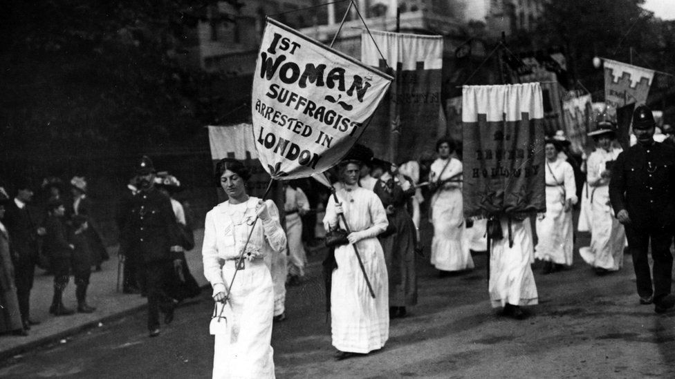 Women wearing long white gowns walk with with placards during a suffragette protest