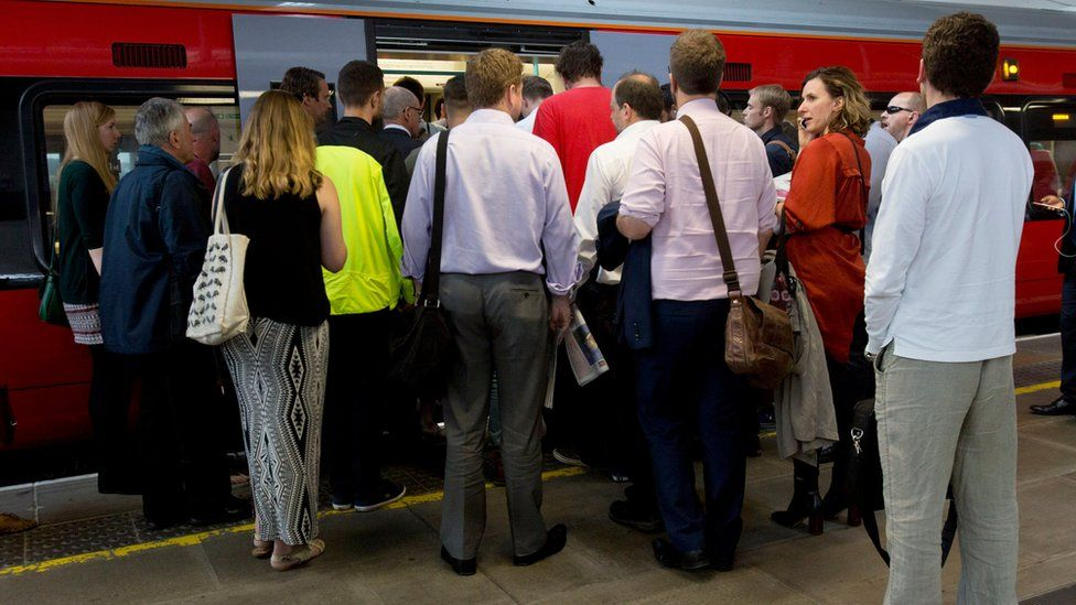 People queuing to get on a train