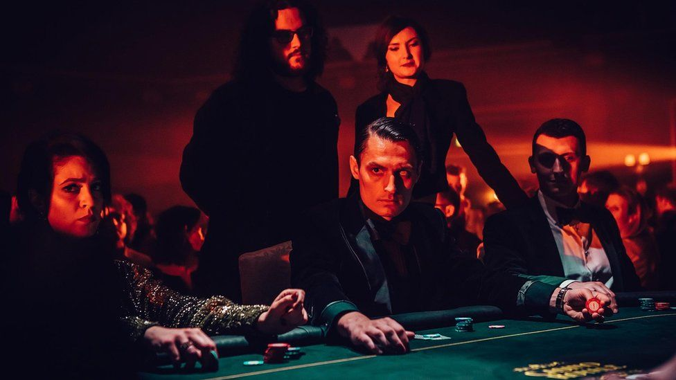 Players sit at a card table in costume, with the main villainous actor, blinded in one eye, starting at the camera - an example of the productions that go on around the film