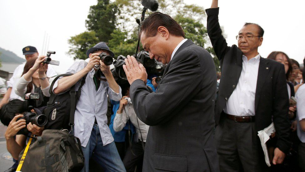 """Governor of Japan""""s Kanagawa prefecture Yuji Kuroiwa (C) prays to mourn victims as he visits a facility for the disabled, where a deadly attack by a knife-wielding man took place, in Sagamihara, Kanagawa prefecture"""