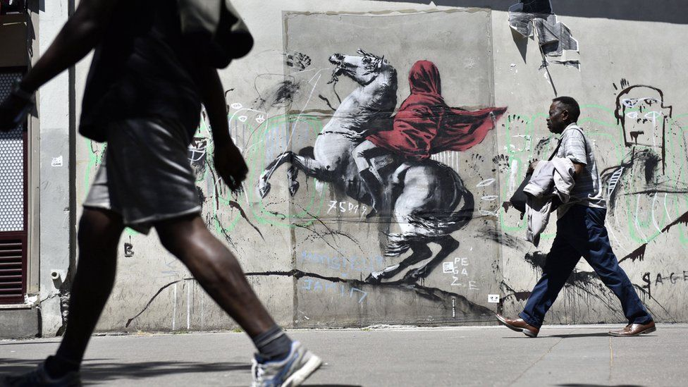 People walk by a recent artwork believed to be attributed to Banksy showing Napoleon rearing his horse, wrapped in a red cloak in the 19th district of Paris