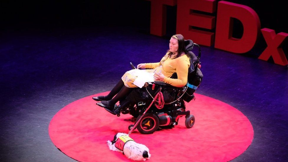 Lucy Watts speaking at a TedX event with her support dog Molly at her side