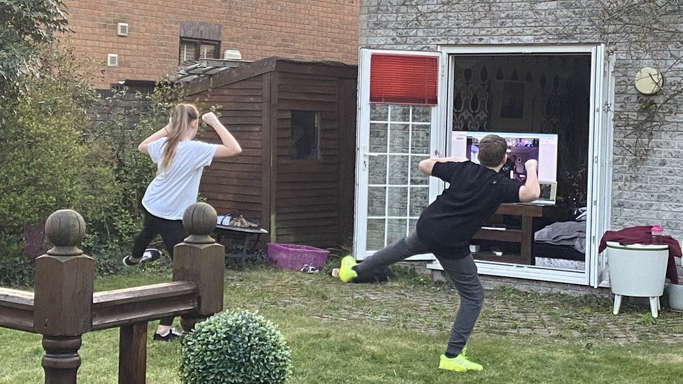Two people doing exercise in their garden