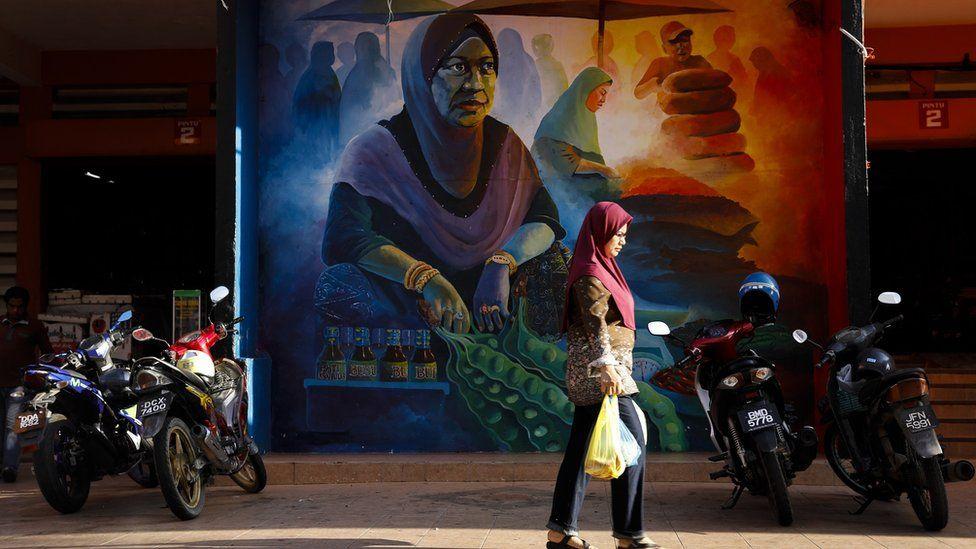A woman walks past a mural at the central Siti Khadijah market