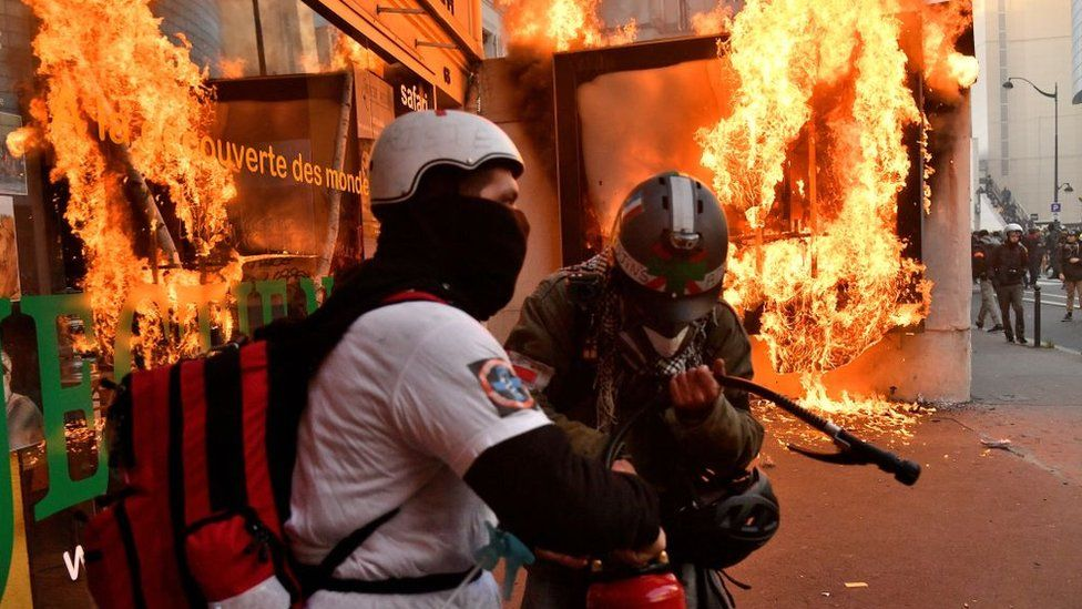 Firefighters try to extinguish the flames after protesters burn a billboard during a protest against the government's pension overhaul in Paris, France, January 11, 2020