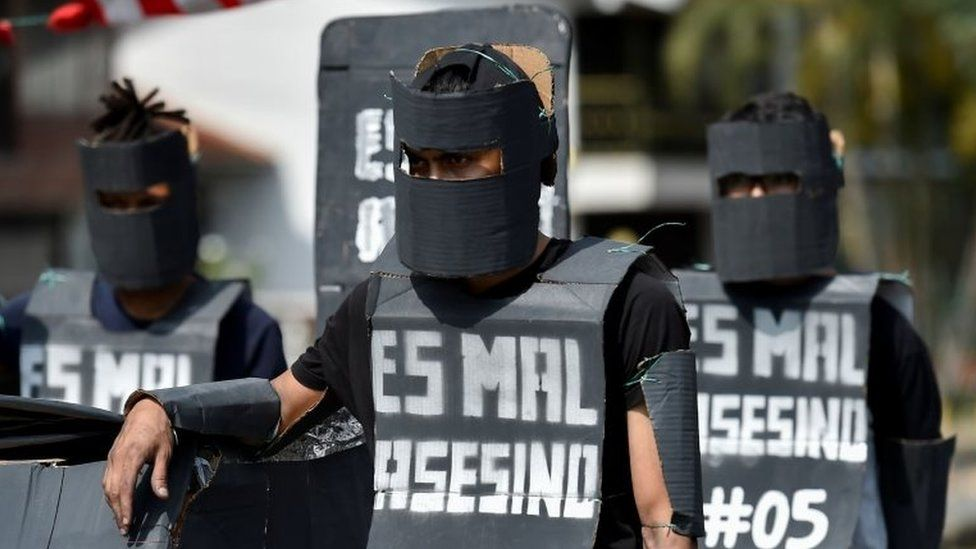 University students fancy dressed as members of the Mobile Anti-Disturbances Squadron (Esmad), demonstrate during a protest against the government of Colombian President Ivan Duque in Cali, Colombia, on December 4, 2019
