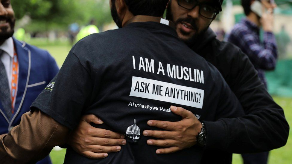 """A man hugs another man, wearing a t-shirt saying """"I am a Muslim, ask me anything?"""""""