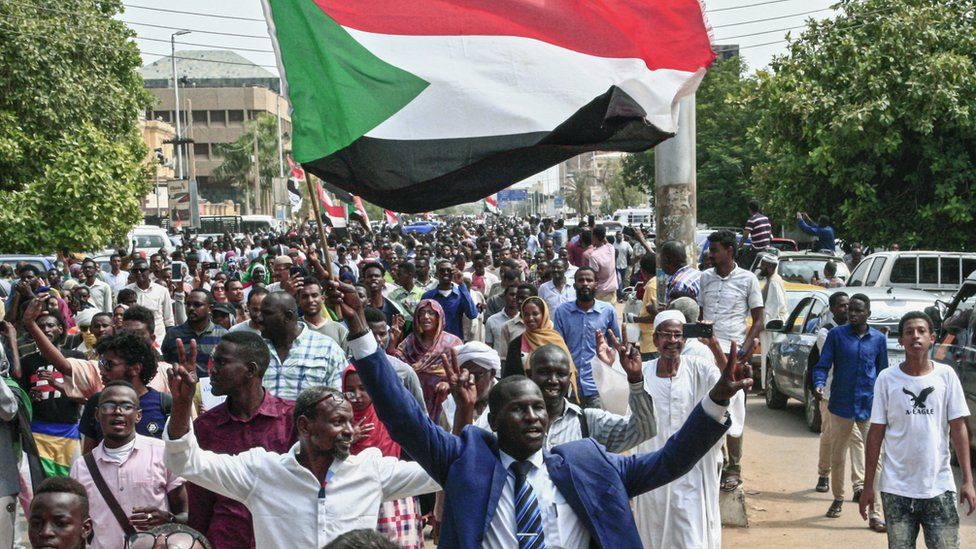 A man flashes the victory gesture while waving a Sudanese national flag during a mass demonstration