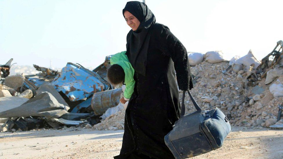 A Syrian woman carries her child in one hand and a bag in the other, as she flees rebel-held eastern neighbourhoods of Aleppo into the Sheikh Maqsoud area that is controlled by Kurdish fighters (photo provided by The Rumaf) (27 November 2016)