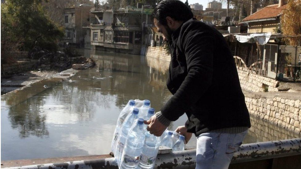 Syrian man holds bottles filled with water in Damascus, Syria, 29 December 2016.