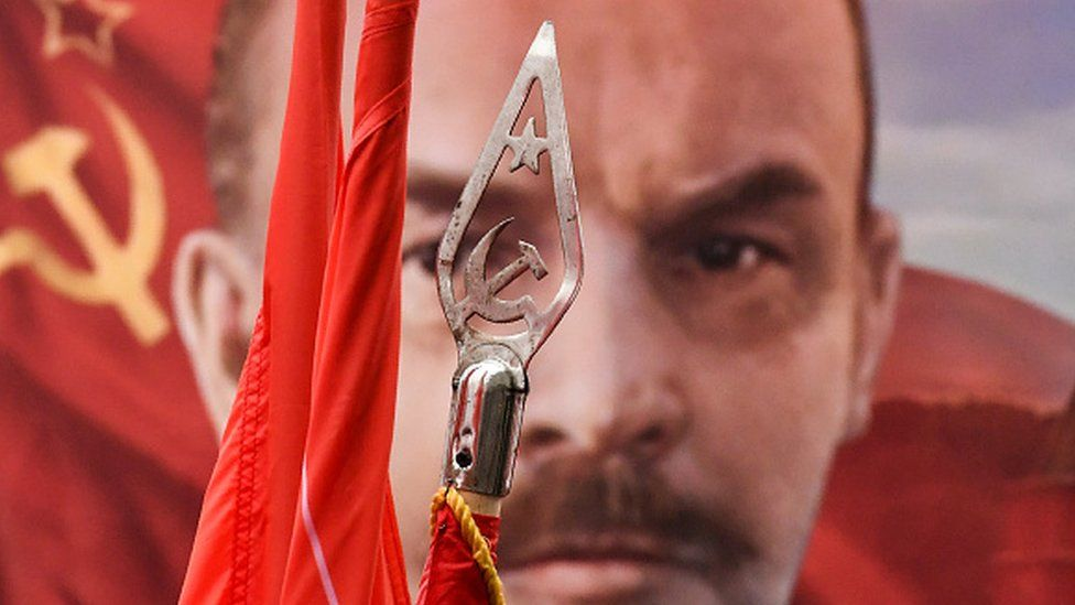 Red flags and a portrait of the Soviet Union founder Vladimir Lenin from a 7 November rally