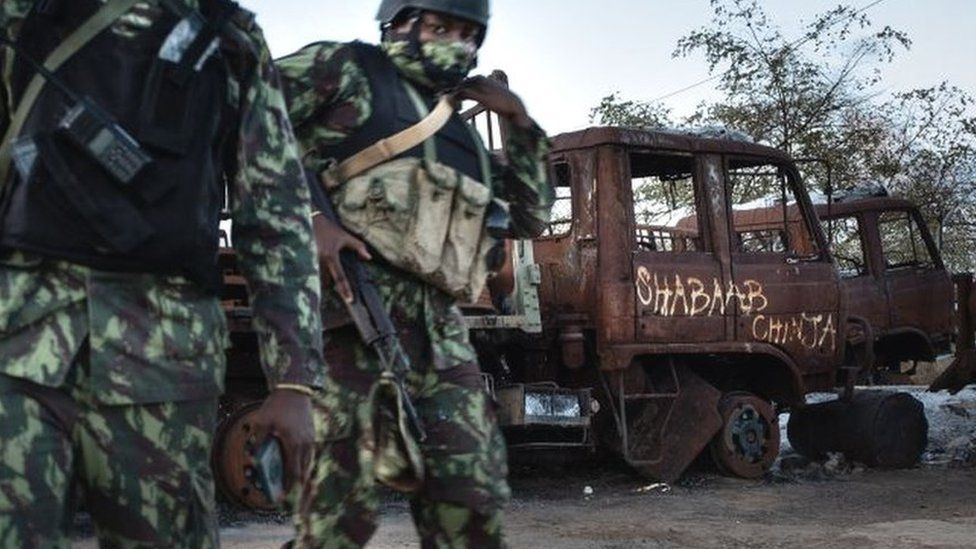 Mozambican soldiers patrol in front of a burned truck carrying the inscription
