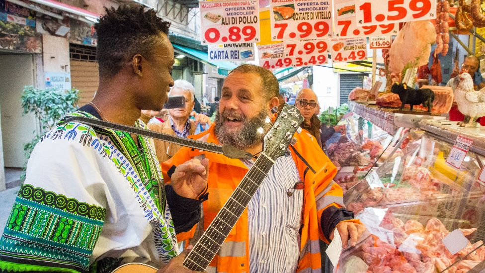 Singer Chris Obehi being created by Sicilians at a butcher's shop in Sicily