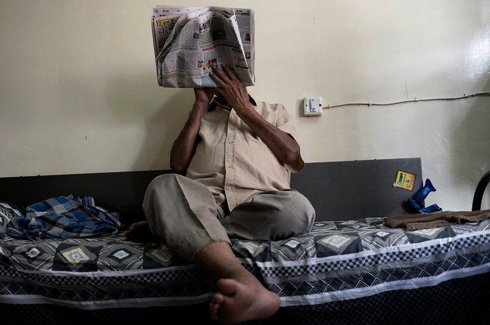 Mr Paramswar reading a newspaper