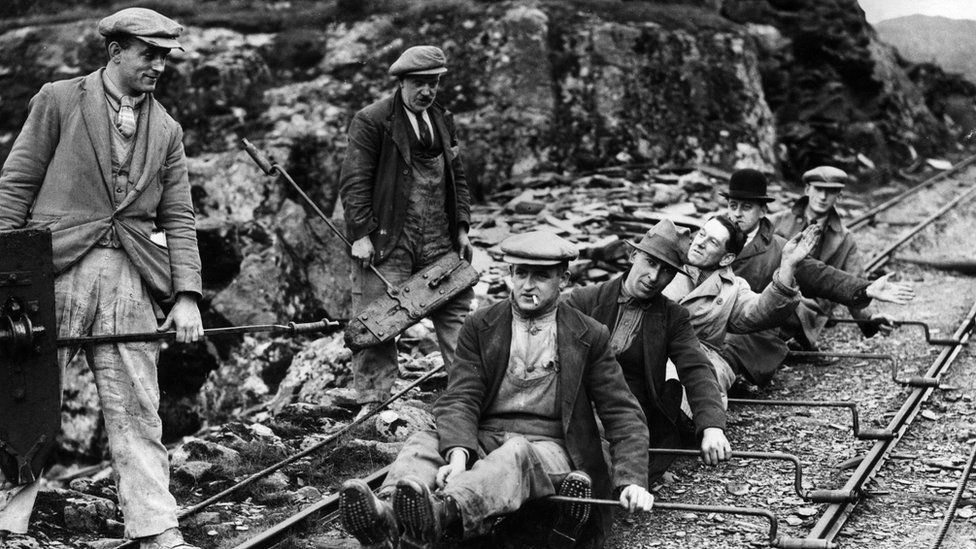 Photo of quarrymen using the rail lines to slide down towards home