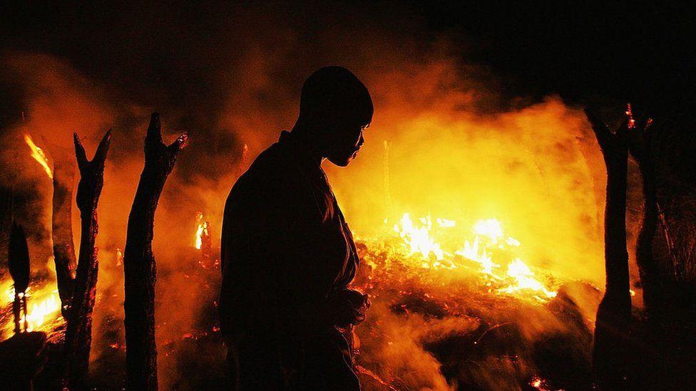 Un combattant rebelle soudanais du Mouvement pour la justice et l'égalité (JEM) regarde sombrement le village abandonné de Chero Kasi brûler moins d'une heure après que les miliciens Janjaweed l'ont incendié dans la violence qui sévit dans la région du Darfour le 7 septembre 2004.