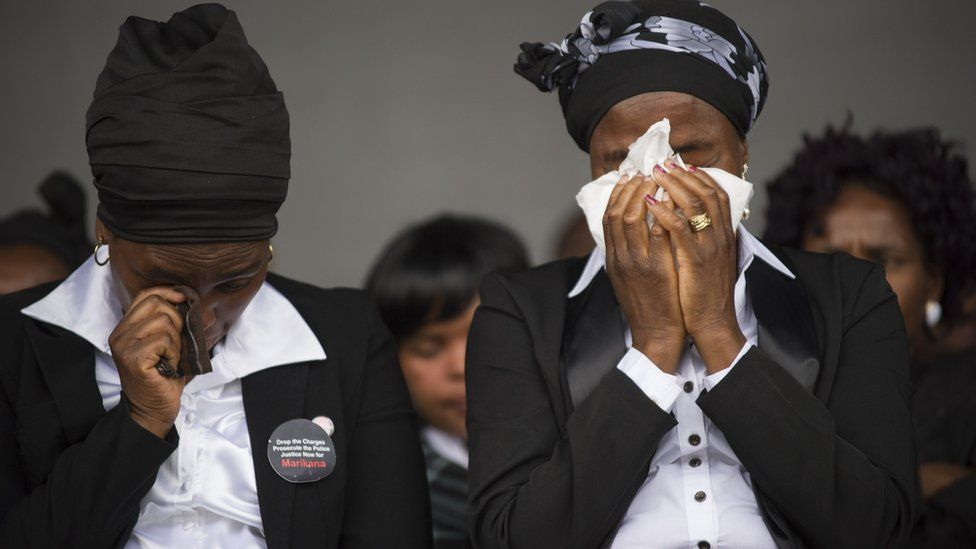Widows cry on August 16, 2014, in Marikana, during a ceremony in tribute to miners who where gunned down by the South African police during a violent wave of strikes two years ago.