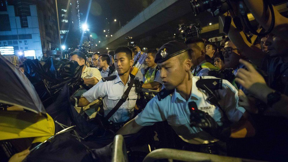 """Police use pepper spray to stop protesters charging outside the Chinese Liason Office in Hong Kong on 6 November 2016, during a protest against an expected interpretation of the city's constitution - the Basic Law - by China's National People""""s Congress Standing Committee (NPCSC) over the invalid oath-taking attempts by newly elected lawmakers Baggio Leung and Yau Wai-ching at the Legislative Council last month."""