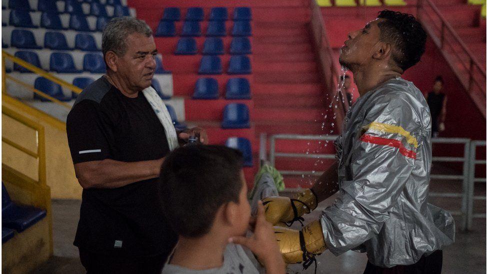 Boxer Ramiro Blanco throws water on his face during training