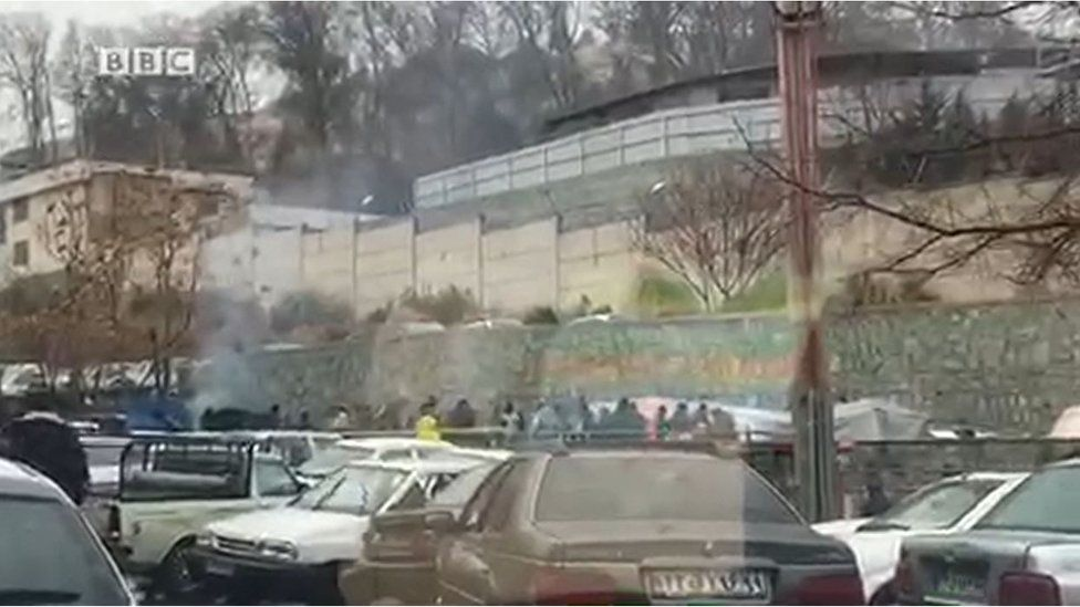 A screen grab shows exterior view of Evin Prison in Tehran with crowd gathered and some tents