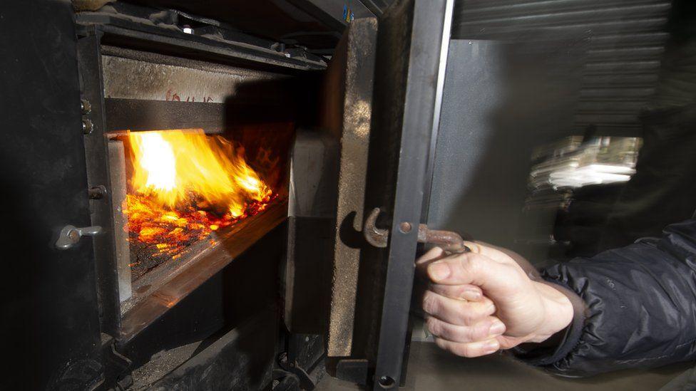 Hand opens boiler door