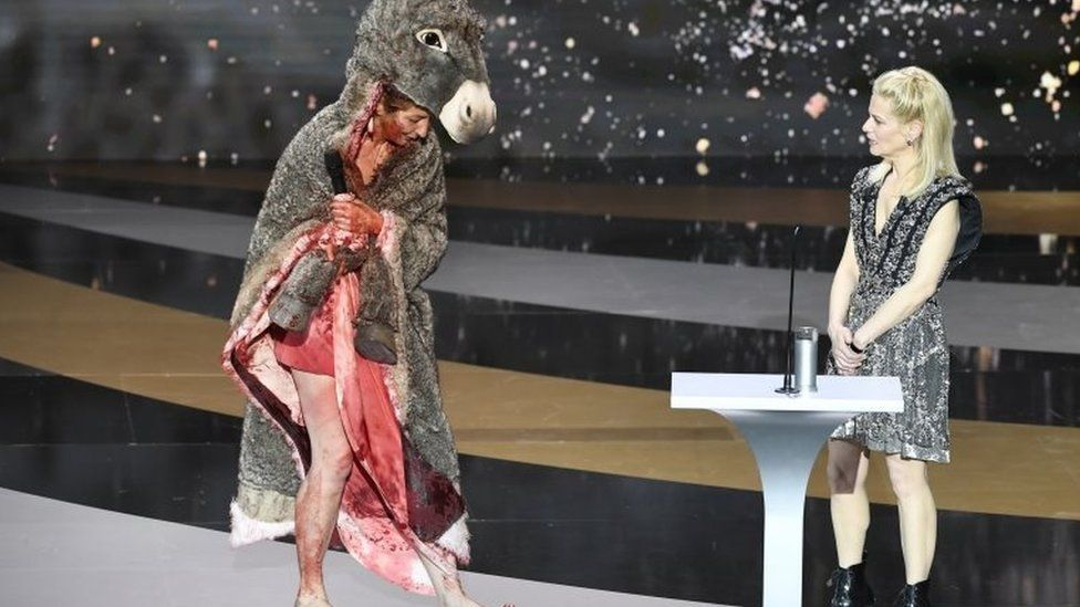 French actress Corinne Masiero (left) wears a donkey costume on top of a bloodied dress in Paris, France. Photo: 12 March 2021