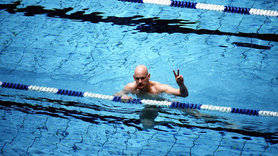 Duncan Goodhew giving a v sign after winning an Olympic gold medal