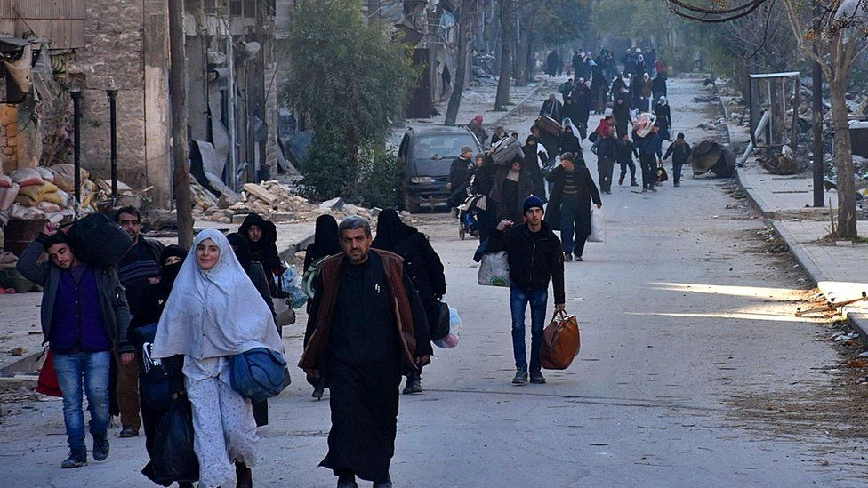 Syrian residents evacuate eastern Aleppo through Bab al-Hadid district on 7 December 2016