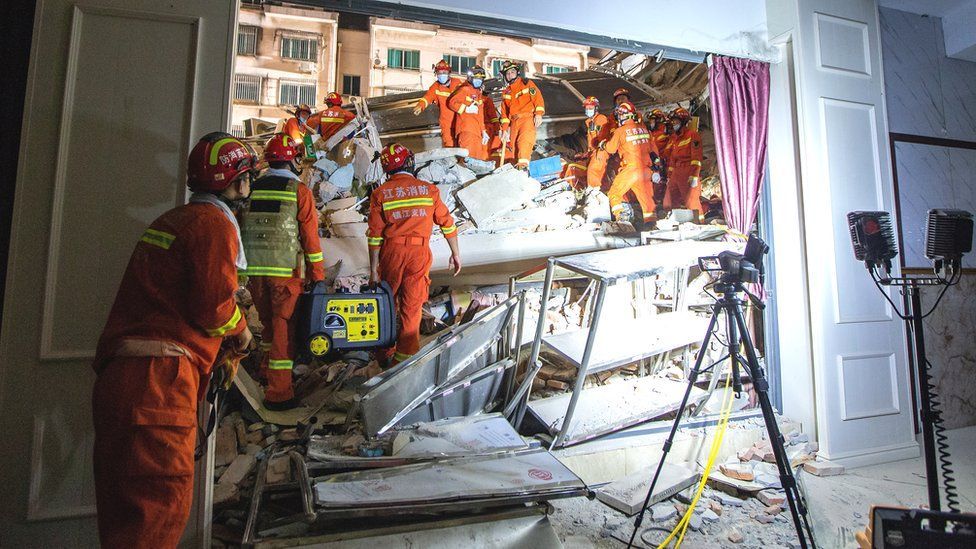 Rescue workers work at the site where a hotel building collapsed in Suzhou, Jiangsu