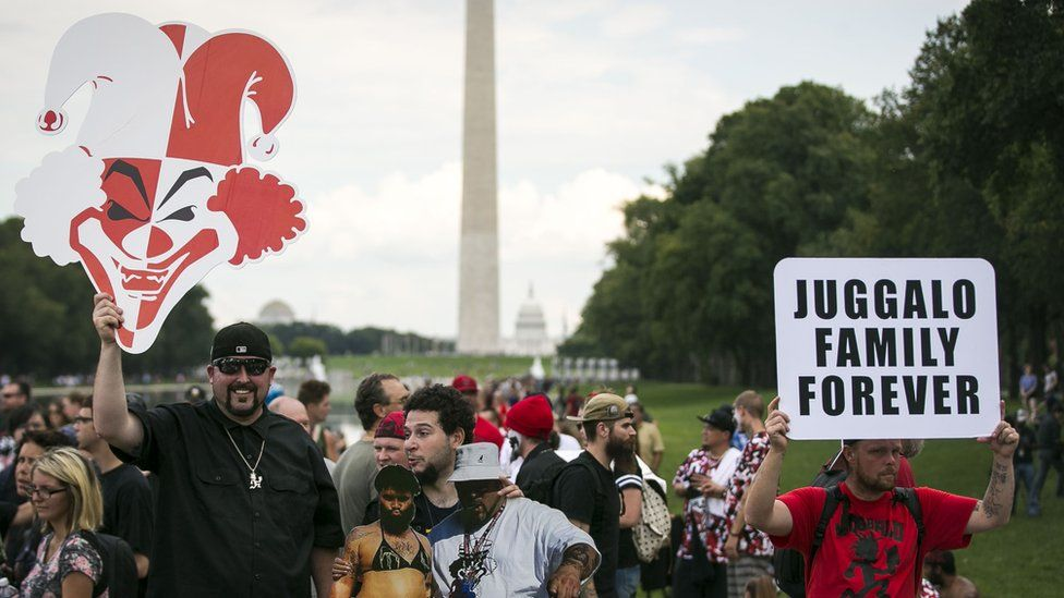 A man holds up a giant cut out of a clown face during the rally in Washington