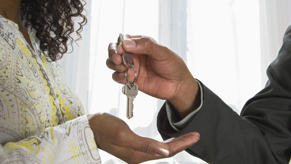 Man handing house keys to woman