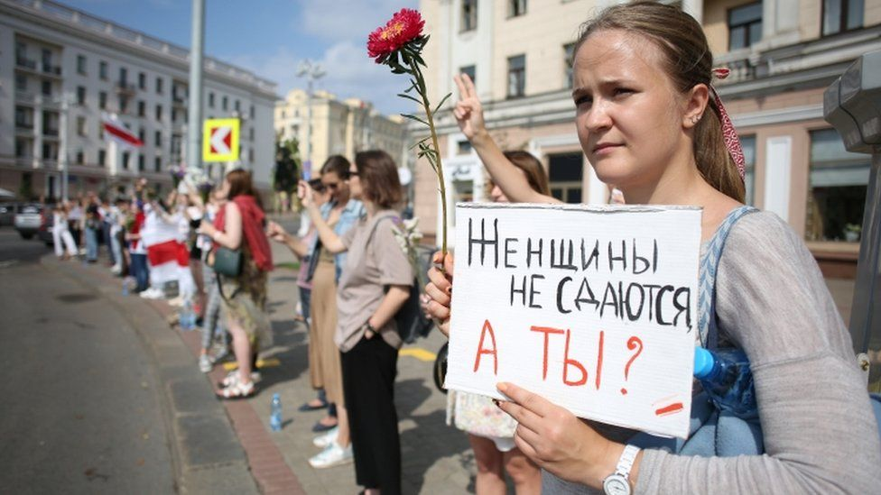 """Protester in Minsk holds up sign saying: """"Women don't surrender, and you?"""""""