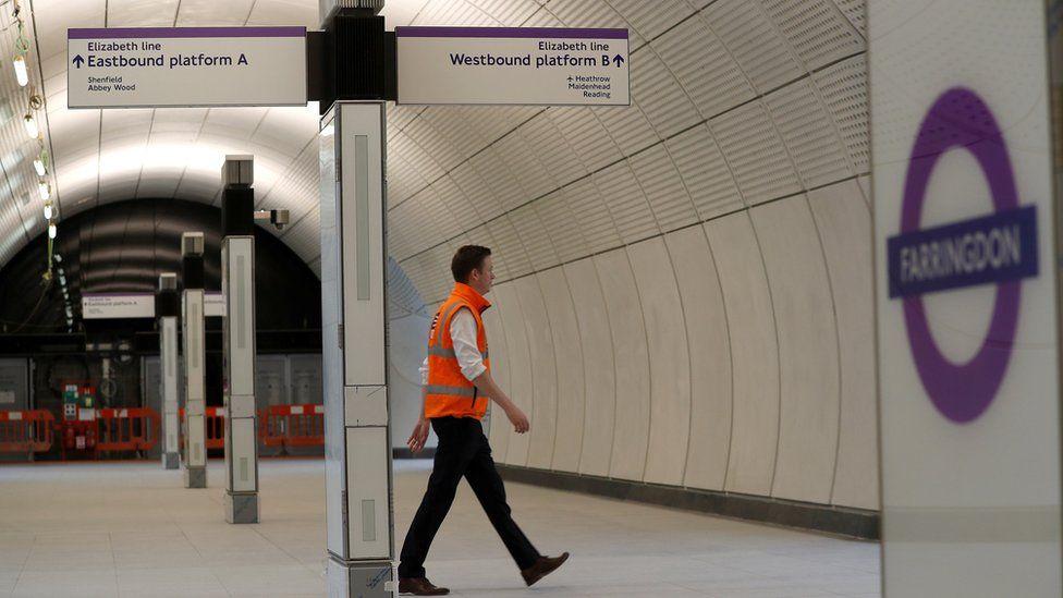 A Crossrail employee walks in the new Farringdon underground station of the Elizabeth line