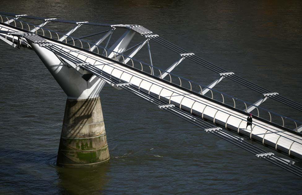 A woman walks across an empty Millennium Bridge during rush hour