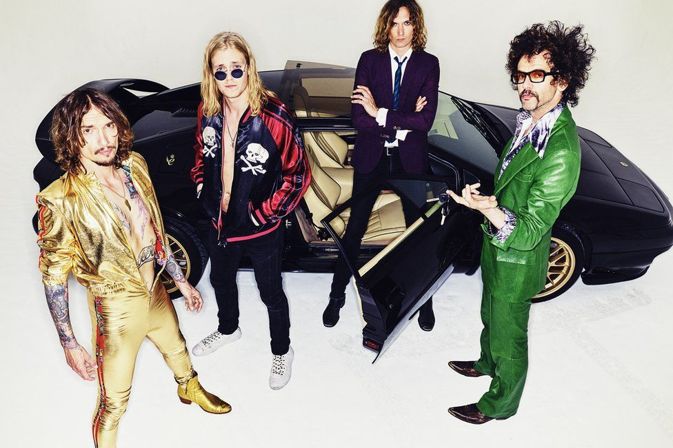 The members of the Darkness stood next to a car
