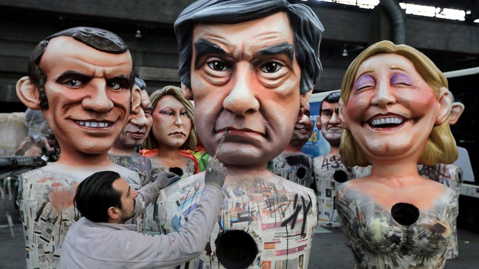 A worker puts the final touches to a giant figure of Francois Fillon (C), former French prime minister, member of The Republicans political party and 2017 presidential candidate of the French centre-right, next to French National Front leader Marine Le Pen (R) and Emmanuel Macron (L), head of the political movement En Marche !, or Onwards !, during preparations for the carnival parade in Nice, France, 2 February 2017