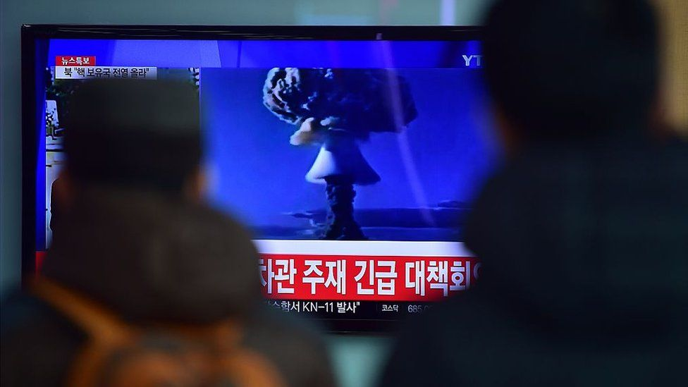 People watch a news report on North Korea's first hydrogen bomb test on 6 January 6 2016