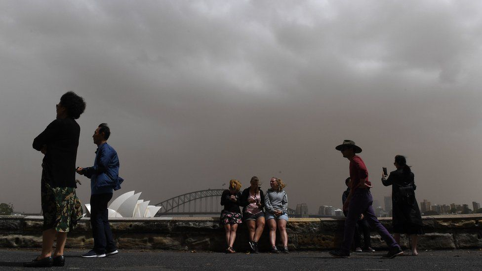 Tourists in Sydney framed against a thick dust-filled sky