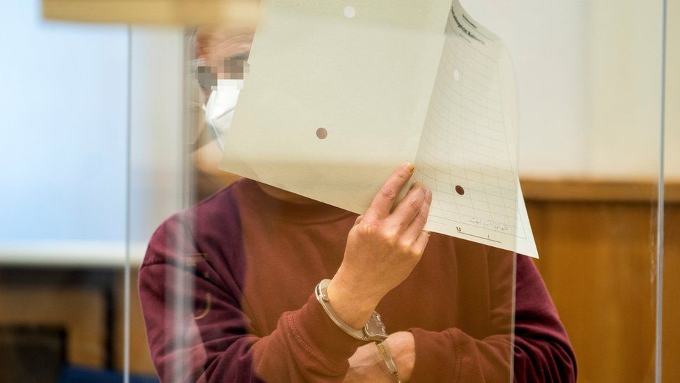 Former Syrian intelligence officer Eyad al-Gharib holds up a file in court in Koblenz, Germany (24 February 2021)
