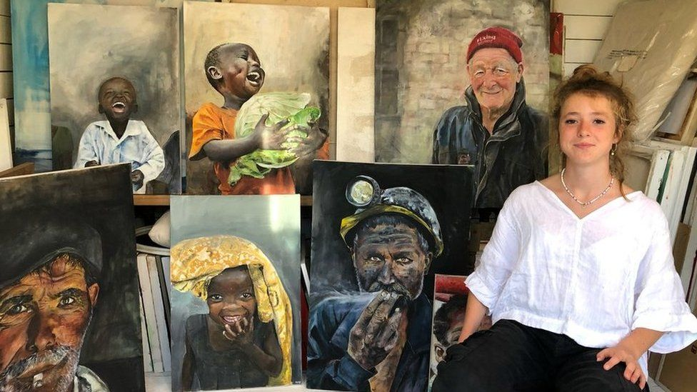 Makenzy Beard, 14, with a selection of her paintings