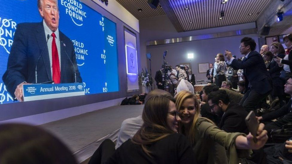 Participants watch the appearance of US President Donald J. Trump on screen from an adjacent room, during the 48th Annual Meeting of the World Economic Forum (WEF) in Davos, Switzerland, 26 January 2018