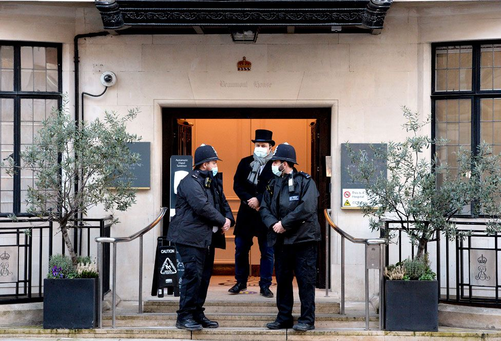 Police officers stand outside an entrance to the King Edward VII Hospital in London