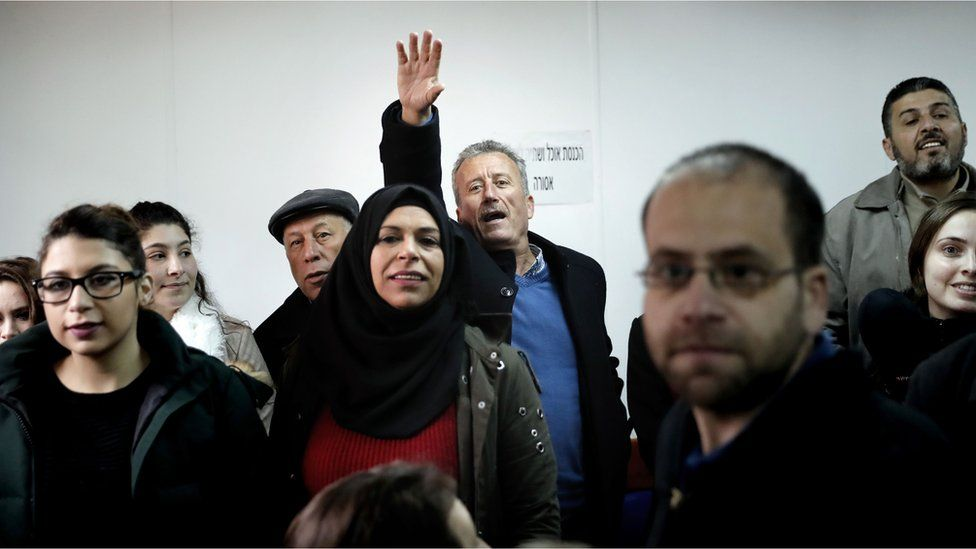 Basseem Tamimi, Ahed's father, waves to her from the back of a crowded court room when she arrives
