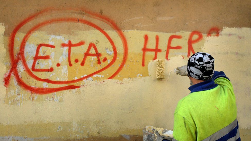 """A municipal worker paints over graffiti reading """"Eta, the people are with you"""" in the Basque town of Guernica, Spain, 21 October 2011, the day after the Basque separatist group announced a definitive cessation of armed activity"""