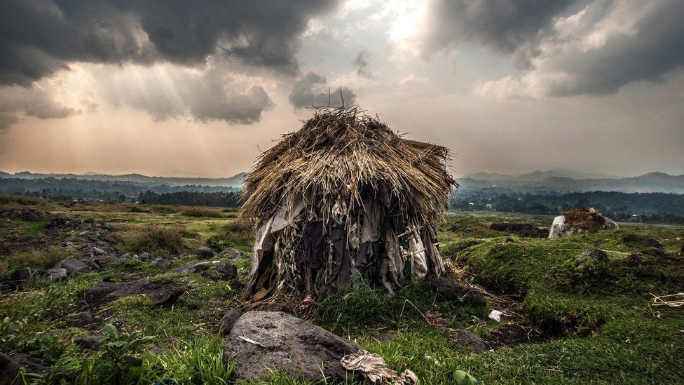 single thatched hut in the middle of a deep green landscape, with broken rays of sunlight breaking through the cloud